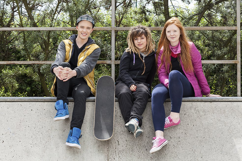 Young friends sitting on a halfpipe in a skatepark